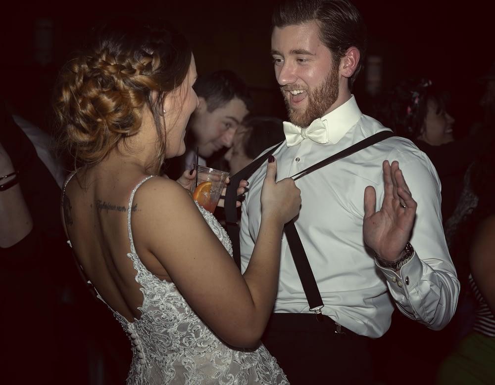 eastern shore weddings photo of bride and groom dancing, bride is pulling groom's suspenders