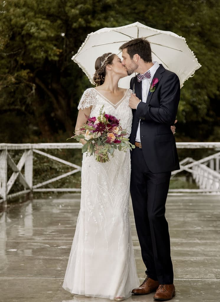 eastern shore weddings photo of bride and groom standing in the rain under an umbrella